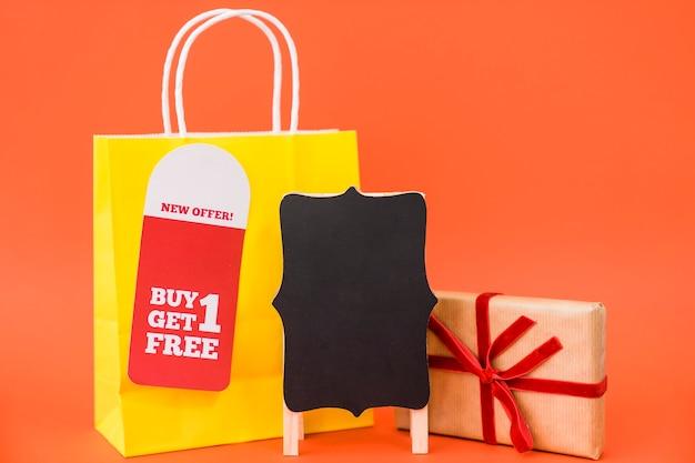Conceito de venda de sexta feira preta com bolsa e caixa de presente atrás do tábua Foto gratuita