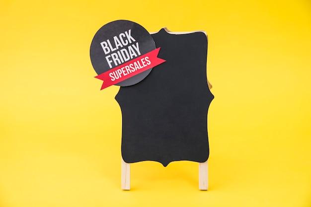 Conceito de vendas de sexta feira preta com placa em fundo amarelo Foto gratuita