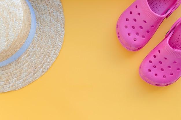 Conceito de verão com acessórios para praia. fundo de férias viagens. chinelos, sandálias, chapéu de palha sobre um fundo amarelo. itens de férias e viagens. vista superior. Foto Premium