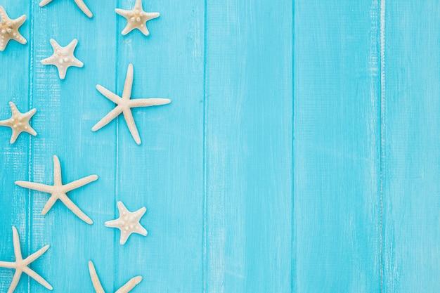 Conceito de verão com estrela do mar em um fundo azul de madeira com espaço de cópia Foto gratuita