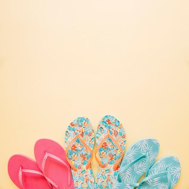 Conceito de verão com três pares de chinelos Foto gratuita