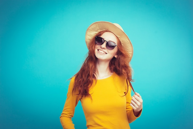 Conceito de viagem - close up retrato jovem e bonita menina redhair atraente com chapéu de moda e sorvete sorrindo. fundo pastel azul. copie o espaço. Foto gratuita