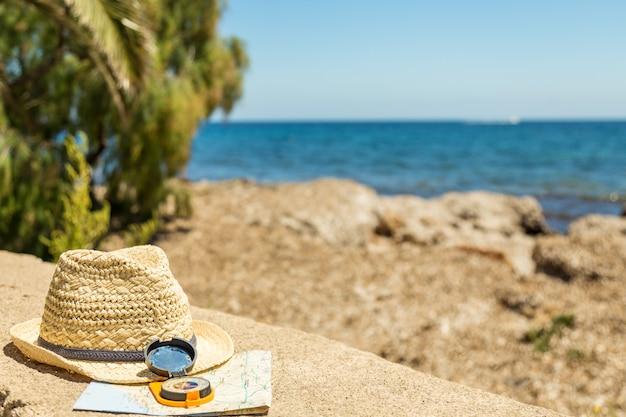 Conceito de viagem com um mapa, uma bússola e chapéu de palha Foto Premium