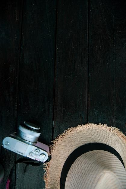 Conceito de viagens de vista superior com câmera e chapéu na mesa Foto gratuita