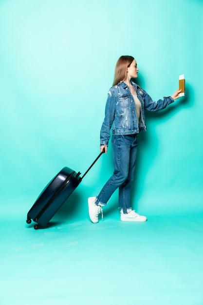 Conceito de viagens. menina mulher feliz com mala e passaporte na parede de cor verde Foto gratuita