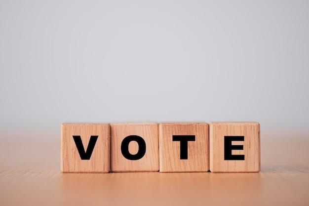 Conceito de voto e eleição, tela de impressão de formulação de voto no bloco de cubos de madeira. Foto Premium