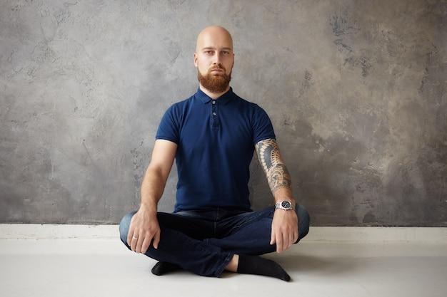 Conceito de zen, ioga e meditação. foto isolada de um cara barbudo bonito com a cabeça raspada sentado no chão de madeira com as pernas cruzadas, mantendo uma expressão facial calma, meditando com os olhos abertos Foto gratuita