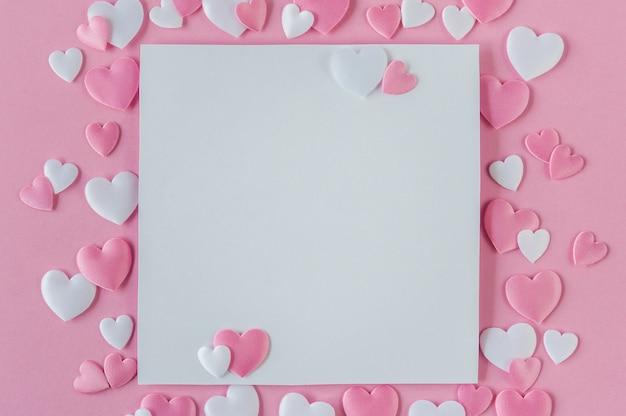 Conceito dia dos namorados cartão com corações rosa e brancos e espaço para texto em um fundo rosa. vista do topo. postura plana. fechar-se. Foto Premium