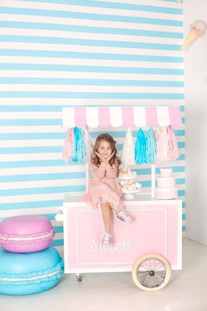 Conceito do aniversário e da felicidade - menina feliz que senta-se em um trole com gelado e doces contra de uma barra de chocolate. bolo multi-colorido grande. quarto decorado para uma aniversariante Foto Premium