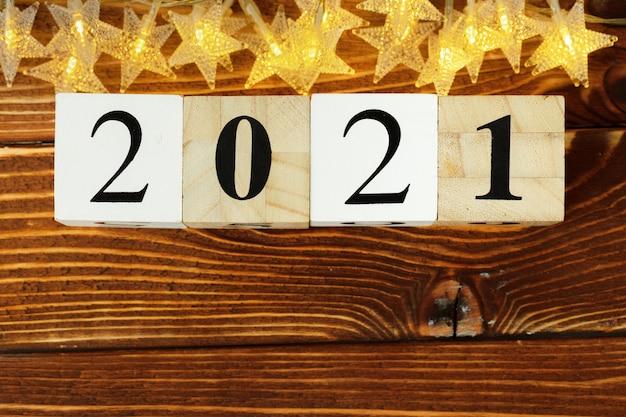 Conceito do ano 2021. estrelas douradas com 2021 números na mesa de madeira Foto Premium