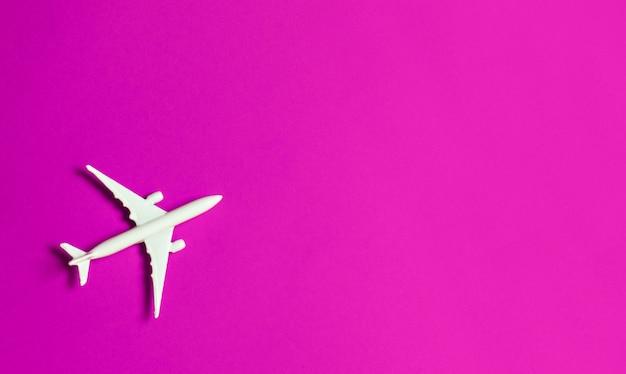 Conceito do curso no fundo cor-de-rosa com espaço da cópia. brinquedo do avião no fundo cor-de-rosa da cor. Foto Premium