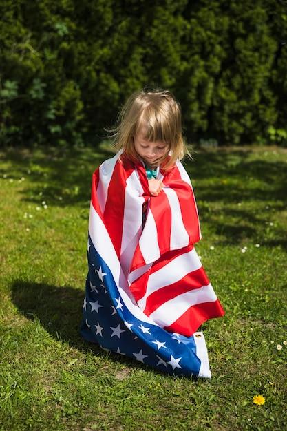 Conceito do dia da independência com a menina no jardim Foto gratuita