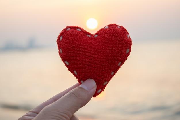 Conceito do dia de valentim, conceito do amor, mão da mulher que guarda o coração vermelho durante o fundo do por do sol. Foto Premium