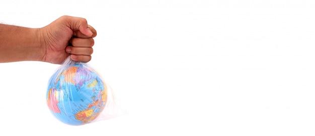 Conceito do dia mundial do meio ambiente. a mão do homem segura a terra em um saco de plástico em branco Foto Premium