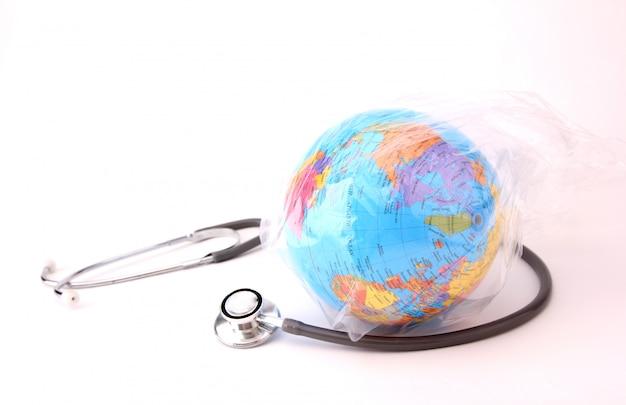 Conceito do dia mundial do meio ambiente. terra em um saco de plástico com um estetoscópio em branco Foto Premium