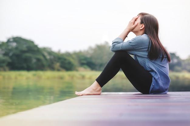 Conceito do dia ruim. mulher de tristeza sentado junto ao rio no pátio de madeira Foto Premium