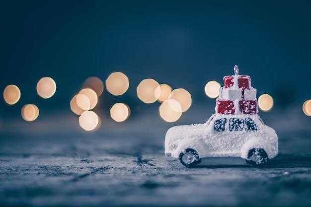 Conceito do feriado do natal com carro do brinquedo e bokeh mágico. copie o espaço. fundo abstrato Foto Premium