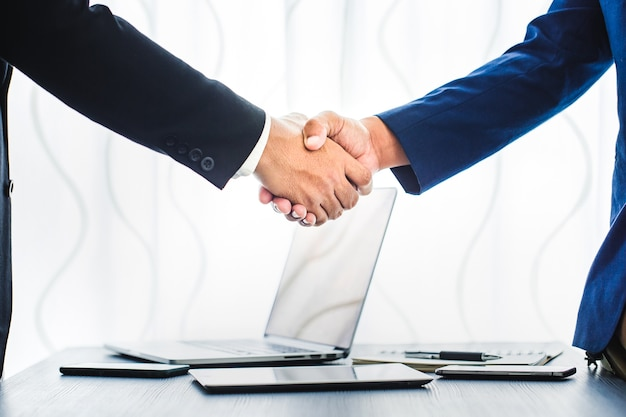 Conceito do negócio, aperto de mão do homem de negócios no espaço de trabalho do escritório para o investimento Foto Premium