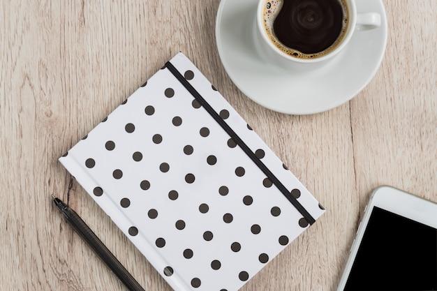 Conceito do negócio e do escritório - caderno preto, branco da tampa do às bolinhas, smartphone e copo do café preto na tabela de madeira. vista do topo. Foto Premium