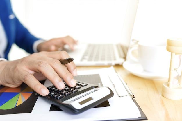 Conceito do plano de contabilidade empresarial, trabalhando no laptop desktop com a calculadora para fazer negócios, mão de homem de negócios trabalhando com o laptop no consultor de investimentos em negócios de mesa de madeira. Foto Premium