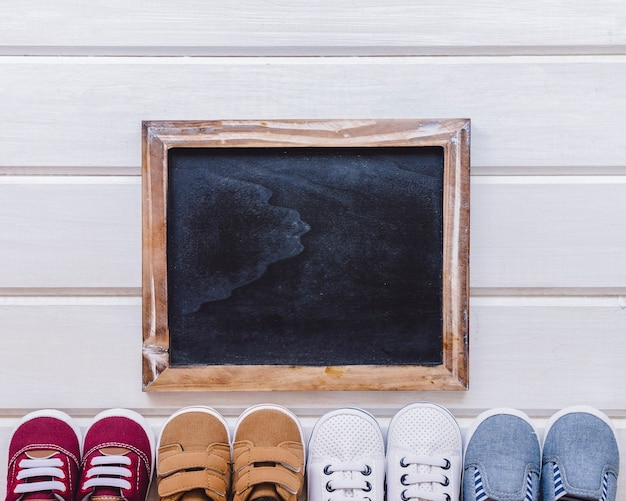Conceito do recém nascido com ardósia e sapatos Foto gratuita