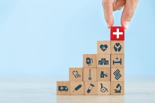Conceito do seguro de saúde, mão que arranja o bloco de madeira que empilha com os cuidados médicos do ícone médicos. Foto Premium