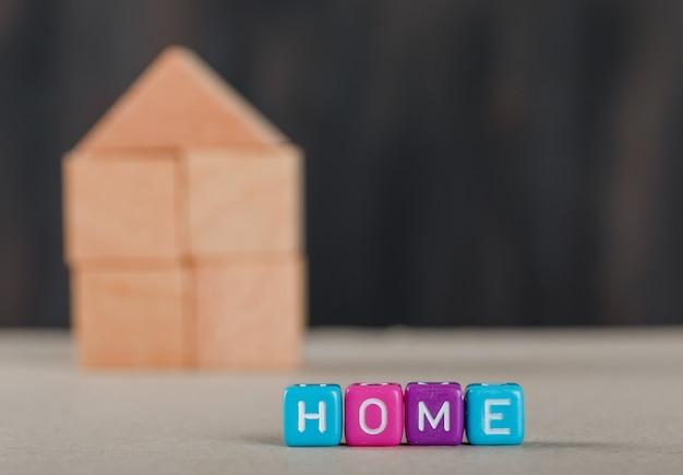 Conceito dos bens imobiliários com cubos coloridos, casa de madeira e branco. Foto gratuita