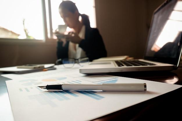 Conceito empresarial com espaço de cópia. mesa de escritório com foco na caneta e quadro de análise, computador, caderno, xícara de café na mesa. tons de entrada. filtro retro, foco seletivo. Foto gratuita