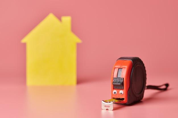 Conceito engraçado de renovação de casa. fita métrica de metal e outros itens de reparo. reparo em casa e conceito redecorado. Foto Premium