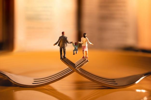 Conceito feliz do equilíbrio da vida da família e do trabalho. miniatura de pai, mãe e filho de mãos dadas e andando no garfo no restaurante Foto Premium
