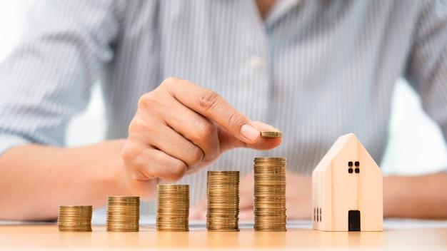 Conceito financeiro de investimento imobiliário e hipoteca de casa, mão de um empresário que está empilhando moedas para investimento imobiliário, economizando para comprar para habitação ou especulação. Foto Premium