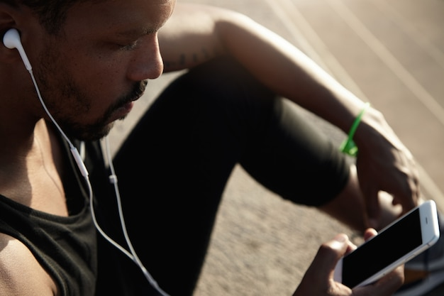 Conceito humano e tecnologia. pessoas e esporte. bonitão africano em fones de ouvido, ouvindo música usando seu telefone inteligente com tela de espaço em branco da cópia para o seu texto de publicidade ou informações Foto gratuita