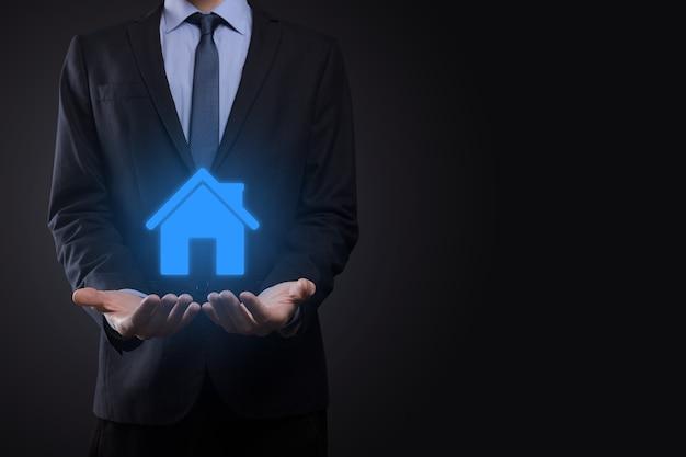 Conceito imobiliário, empresário segurando um ícone de casa. casa disponível. conceito de seguro e segurança de propriedade. protegendo o gesto do homem e o símbolo da casa. Foto Premium