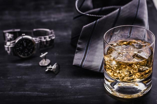 Conceito masculino para o dia dos pais. gravata, relógios, abotoaduras e um copo de uísque com gelo Foto Premium