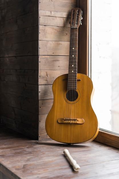 Conceito minimalista com paredes de madeira e violão clássico Foto gratuita
