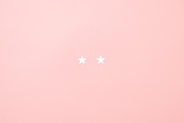 Conceito mínimo do leitão do natal feito dos confetes de prata da estrela no fundo cor-de-rosa. Foto Premium
