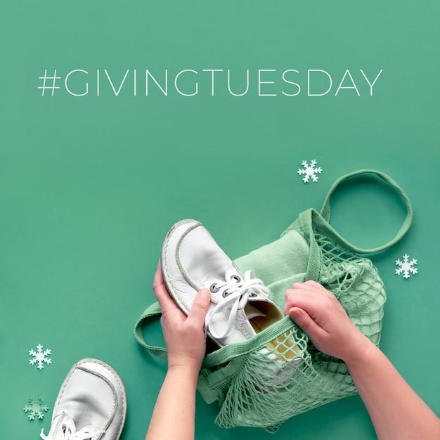 Conceito plano leigos com as mãos, embalagem de sapatos e roupas em saco de malha. dê mercadorias na doação de terça-feira, participando da campanha de doações. colete bens indesejados e passe-os para quem precisa. Foto Premium