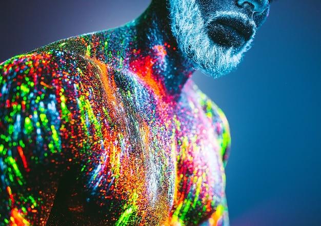 Conceito. retrato de um homem barbudo. o homem é pintado em pó ultravioleta. Foto Premium
