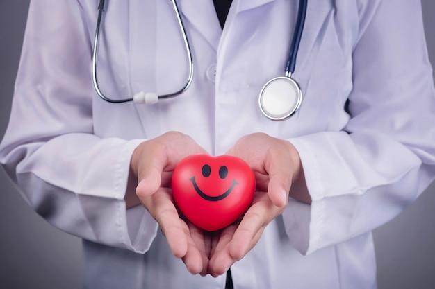 Conceito saudável - bola de coração vermelho na mão de um médico e um estetoscópio azul Foto Premium