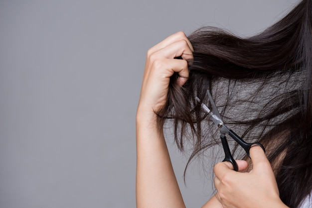 Conceito saudvel. mão de uma mulher segurando uma tesoura e cortar o cabelo comprido danificado Foto Premium