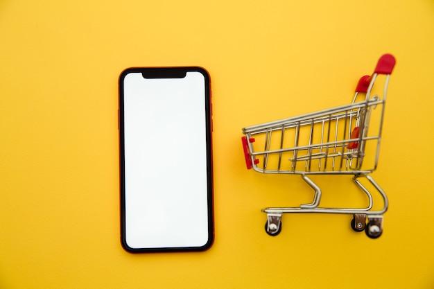 Conceitos de compras online com maquete de carrinho e smartphone em fundo amarelo. mercado de comércio eletrônico. logística de transporte. varejo comercial. Foto Premium