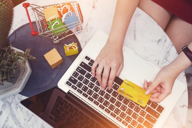Conceitos de compras online, mãos de mulher usando cartão de crédito e computador portátil Foto Premium