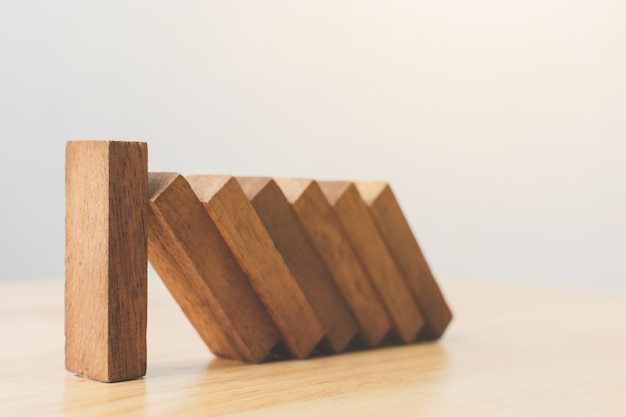 Conceitos de gerenciamento de risco de negócios. bloco de madeira parar de cair de outras peças de efeito dominó. Foto Premium