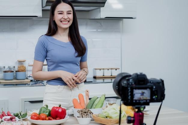 Conceitos de mídia social uma mulher feliz em pé na cozinha usando uma câmera e gravando vídeo online vlogger de mulher asiática feliz transmitindo vídeo online ao vivo ensinando a cozinhar na cozinha em casa. Foto Premium
