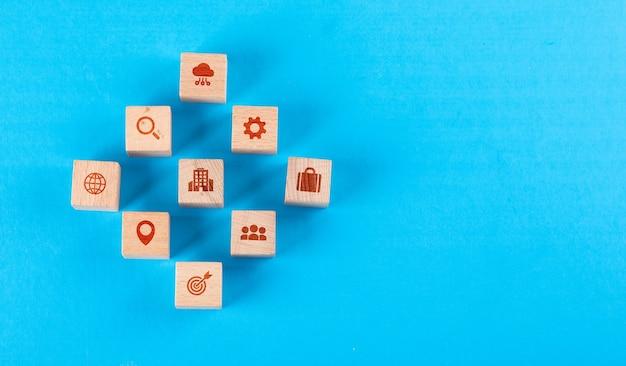 Conceitual de centro médico com blocos de madeira com ícones na mesa plana azul leiga. Foto gratuita