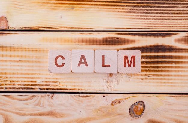 Conceitual de motivação com blocos de madeira com digitado nele calma na mesa de madeira plana leigos. Foto gratuita