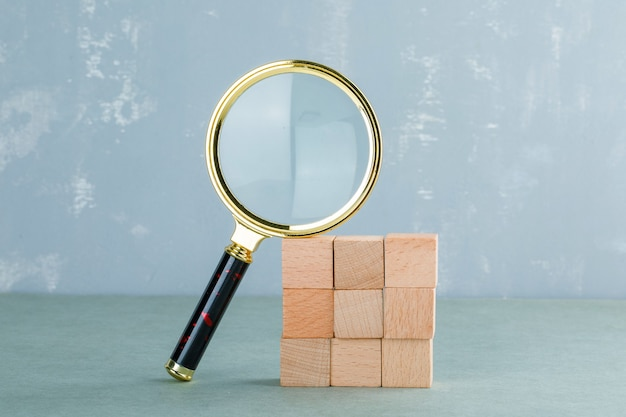 Conceitual de pesquisa com blocos de madeira, vista lateral da lupa. Foto gratuita