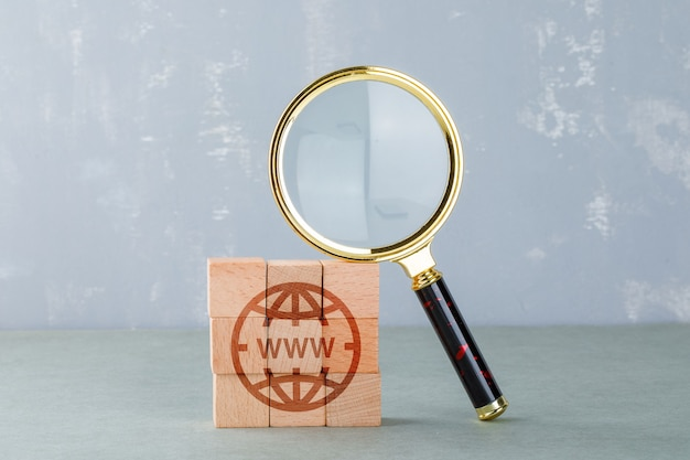 Conceitual de pesquisa na internet com blocos de madeira com o ícone da internet, vista lateral da lupa. Foto gratuita