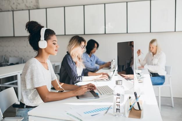 Concentrada web designer feminina africana usando tablet gráfico enquanto seus colegas escrevem relatórios. retrato interno de programadores de empresa internacional passando algum tempo juntos no local de trabalho. Foto gratuita