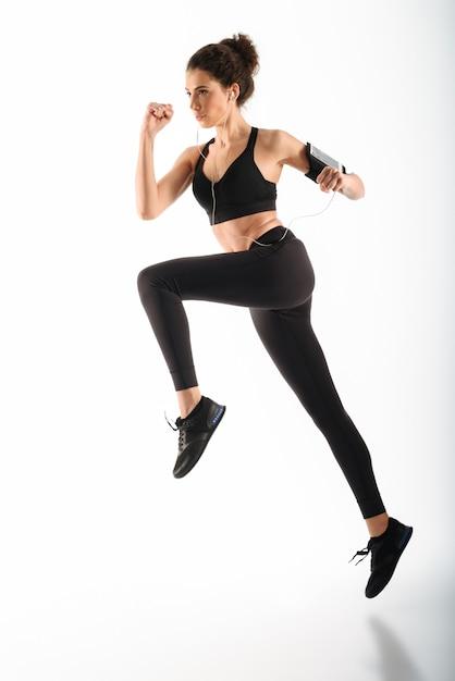 Concentrado encaracolado morena fitness mulher correndo e ouvindo música Foto gratuita